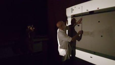 Dans une des chambres noires du laboratoire, la photographe Sara Imloul (à gauche dans l'obscurité) et Diamantino Quintas (dans la lumière) travaillent sur le tirage d'une photo d'art d'une pièce d'assemblage du sculpteur Nicolas Lefebvre. Photo © Pierre d'Ornano