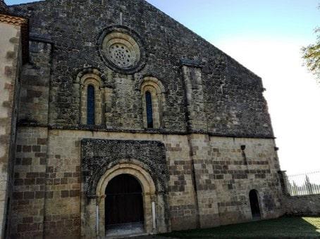 """Façade romane de l'abbatiale de Flaran. Cette façade occidentale (XIIe – XIIIe siècles) est soulignée par deux contreforts. Le porche, sans tympan, qui repose sur les colonnes de piédroits, s'ouvre par une triple voussure. Deux ouvertures en plein cintre, surmontées d'une rose (""""oculus""""), laissent pénétrer la lumière du couchant, dans la nef. Bâtie en pierre de taille vers 1180, l'église Notre Dame de Flaran est remarquable par ses proportions, par la rigueur de son plan cistercien et par son état de conservation, malgré des dimensions modestes (40 m de long par 19 m de large). Elle demeure caractéristique de l'art roman méridional de la deuxième moitié du XIIe siècle. Photo © François Collombet"""