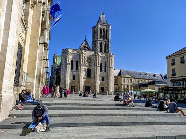 Parvis de la cathédrale -basilique de Saint-Denis. Aujourd'hui, population et religions diverses se retrouvent à portée de ses trois portails conçus au XIIe siècle par l'abbé Suger. Saint-Denis est la nécropole des rois et reines de France. Construite sur la tombe de saint Denis, évêque missionnaire mort vers 250, l'abbaye royale de Saint-Denis accueille dès la mort du roi Dagobert en 639 et jusqu'au XIXe siècle, les sépultures de 43 rois, 32 reines et 10 serviteurs de la monarchie. En 1966, la basilique fut élevée au rang de cathédrale. Photo © François Collombet